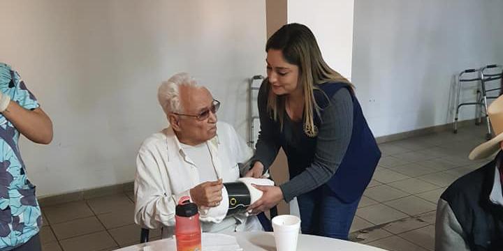Alma Calleros da ayuda a personas de la tercera edad a registrarse para la vacunación